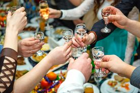 stock photo of vodka  - People hands Clinking glasses with vodka and wine - JPG