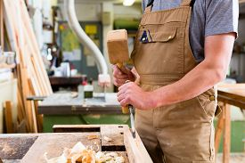 stock photo of chisel  - Carpenter with chisel and hammer - JPG