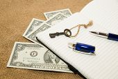 foto of memento  - Opened notebook with a blank sheet pen key and money on the old tissue - JPG