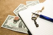 stock photo of memento  - Opened notebook with a blank sheet pen key and money on the old tissue - JPG