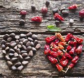 foto of pine nut  - the heart of the dry red pepper pine nuts dogrose on a wooden background - JPG