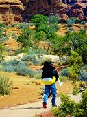 stock photo of big-foot  - A woman wearing yellow pants with a big cast on her foot and ankle and holding a crutch is being gallantly carried piggyback by her boyfriend into a Utah National park - JPG