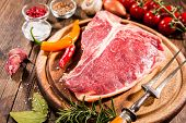 Постер, плакат: Raw fresh meat t bone steak and seasoning on wooden background