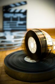 stock photo of mm  - 35 mm cinema film reel and out of focus movie clapper board in background on wooden floor vertical frame - JPG