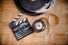 stock photo of mm  - Cinema movie clapper board and 35 mm film reel on wooden floor vintage color effect - JPG
