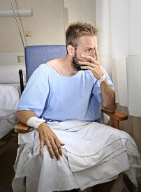 picture of medical condition  - young injured man in hospital room sitting alone in pain looking negative and worried for his bad health condition sitting on chair suffering depression on a sad lonely medical background - JPG