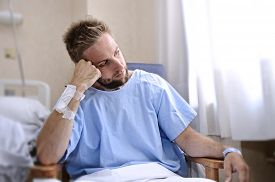 foto of medical condition  - young injured man in hospital room sitting alone in pain looking negative and worried for his bad health condition sitting on chair suffering depression on a sad lonely medical background - JPG