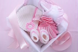 stock photo of pacifier  - Its a Girl pink theme baby shower gift box with baby clothes bib bonnet booties pacifier and socks - JPG