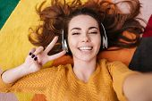 Top view of a smiling pretty girl in headphones showing peace gesture while lying on a carpet at hom poster