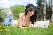 Постер, плакат: Милая женщина с белыми ноутбук в парке с одуванчики