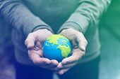 Hands holding environmental conservation globe poster