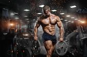 Muscular Athletic Bodybuilder Fitness Model Posing After Exercises In Gym poster