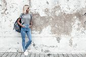 Hipster girl wearing blank gray t-shirt, jeans and backpack posing against rough street wall, minima poster