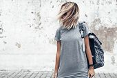 Hipster girl wearing blank gray t-shirt and backpack posing against rough street wall, minimalist ur poster