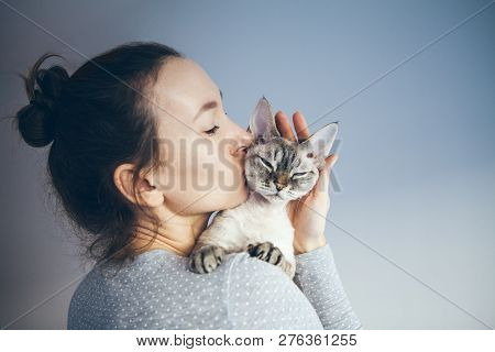poster of Woman Is Kissing And Cuddling Her Sweet And Cute Looking Devon Rex Cat. Kitten Feels Happy To Be Wit