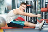 smiling fitness man at back muscles exercises with training weight machine station in gym