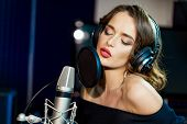 Focused Pretty Singer With Headphones In Front Of The Microphone Recording A Song In Studio. Portrai poster