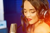 Caucasian Female Singer With Headphones And Closed Eyes Sings At The Mic In A Recording Studio. Port poster