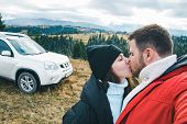Kissing Couple At The Top Of The Hill Suv Car On Background. Beautiful Landscape. Car Travel Tourism poster