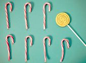 flat lay of red candy canes and lolly pop on blue poster
