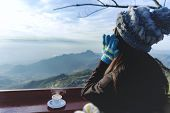 Woman Traveler Drinks Coffee In Restaurant With A View Of The Mountain Landscape. A Young Tourist Wo poster
