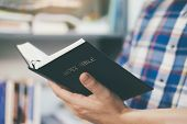 Man Holding And Reading The Holy Christian Bible poster