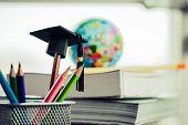 Education Graduate Study Concept: Black Graduation Hat On Pencils, Blur Of Europe Earth World Globe  poster