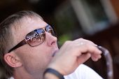 pic of shisha  - The mid adult man is smoking shisha in a cafe - JPG