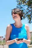 picture of vivacious  - Low angle view of a pretty vivacious woman laughing at the contents of an sms she has just received on her mobile phone - JPG