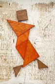 abstract figure of a female dancer built from seven tangram wooden pieces, a traditional Chinese puz