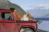 Side view of a mixed race man lying on hood of jeep near mountain lake
