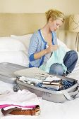 Woman sitting cross legged on bed next to folded clothes and packed suitcase
