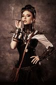 Portrait of a beautiful steampunk woman over grunge background.