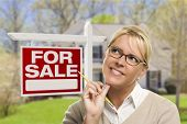 Attractive Young Adult Woman with Pencil in Front of For Sale Real Estate Sign and House.
