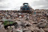 foto of landfills  - Garbage piles up in landfill site each day while truck covers it with sand for sanitary purpose - JPG