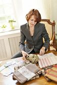pic of interior decorator  - Female interior designer choosing from fabric samples sitting at desk - JPG