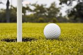 stock photo of caddy  - golf ball on lip of cup on grass  - JPG