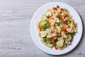 stock photo of marrow  - Italian pasta farfalle with slices of vegetables on a wooden background - JPG