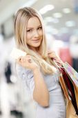 picture of blonde woman  - Portrait of the smiling blonde in shop with a credit card in a hand - JPG