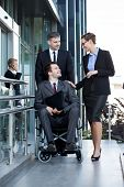 stock photo of worker  - Vertical view of disabled worker and his co - JPG