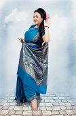 picture of vedic  - Caucasian mature woman posing in blue sari on sky background  - JPG
