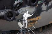 picture of shipbuilding  - man spray painting hood of ship grey in dock - JPG