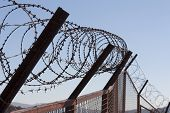 picture of barbed wire fence  - Security with a barbed wire fence photo - JPG