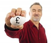 Mature Man Holds A White Nest Egg With British Pound Currency Symbol (£) On It.