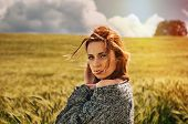 stock photo of breathtaking  - portrait of sensual young red hair woman on breathtaking view of dramatic summer storm sky in the field - JPG