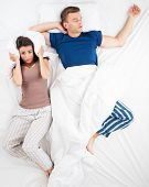 stock photo of irritated  - Top view photo of sleeping snoring man and his irritated wife - JPG
