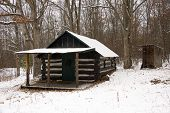 stock photo of log cabin  - An old miners log cabin in a snow covered forest - JPG