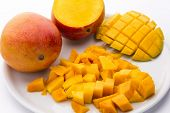 Постер, плакат: Heap Of Juicy Mango Cubes And Whole Fruit On Plate