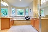picture of tub  - Bathroom with tile trimmed bath tub and two vanity cabinets - JPG