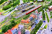 picture of railroad car  - view of toy hobby railroad layout with railway station building passenger and freight cargo trains on rail tracks